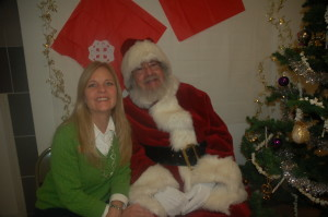 Excited Volunteer Michelle poses with a jolly Santa